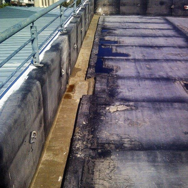 Roof deck waterproofing with enhanced sidewall outlets. Perimeter channel / loose lay paving on support rings with ballast cover